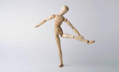 Eine hölzerne Modellpuppe als Sinnbild für eine Person mit einem neuen, künstlichen Hüftgelenk.