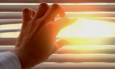 Ein Mann blickt durch die Lamellen einer Jalousie. Er leidet an einer Lichtallergie.