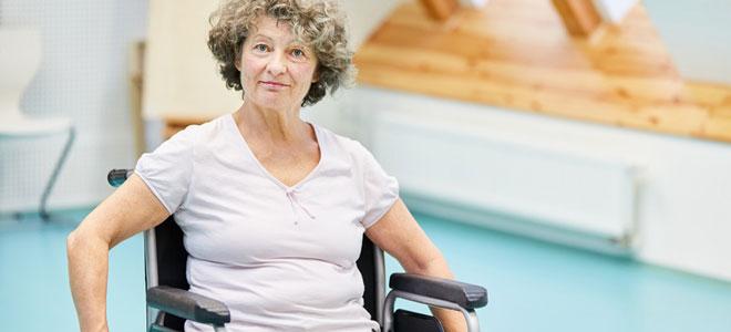 Eine Frau bei der Ergotherapie. Sie sitzt im Rollstuhl, weil sie einen Rückenmarksinfarkt hatte.