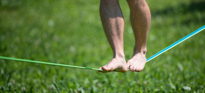 Ein Mann balanciert barfuß auf einer Slackline.