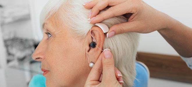 Einer Patientin wird ein Hörgerät eingesetzt.