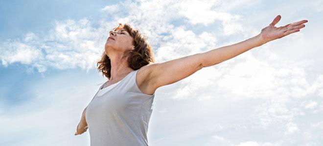 Eine Frau um die 50 macht Atemübungen zur Entspannung.
