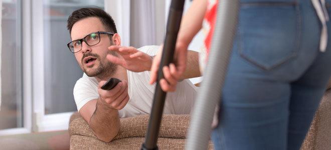 Frau mit Staubsauger, Mann auf Couch