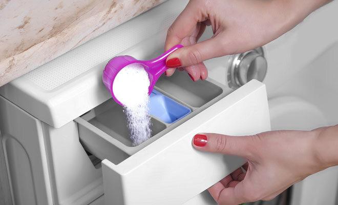 Eine Frau schüttet selbstgemachtes Waschpulver in ein Waschmaschinenfach.