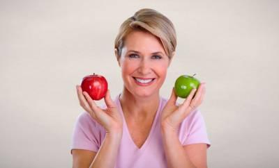 Eine Frau Ende 40 hält zwei Äpfel in den Händen.