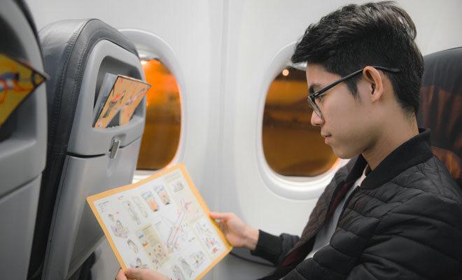 Ein junger Mann liest die Bordinformation im Flugzeug.