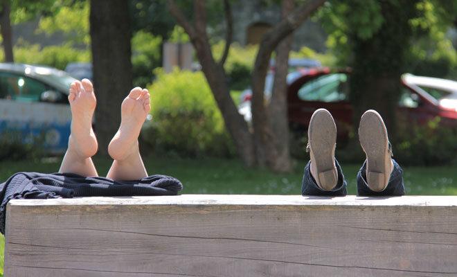 Zwei Personen lagern im Park ihre Füße hoch, weil es sehr heiß ist.