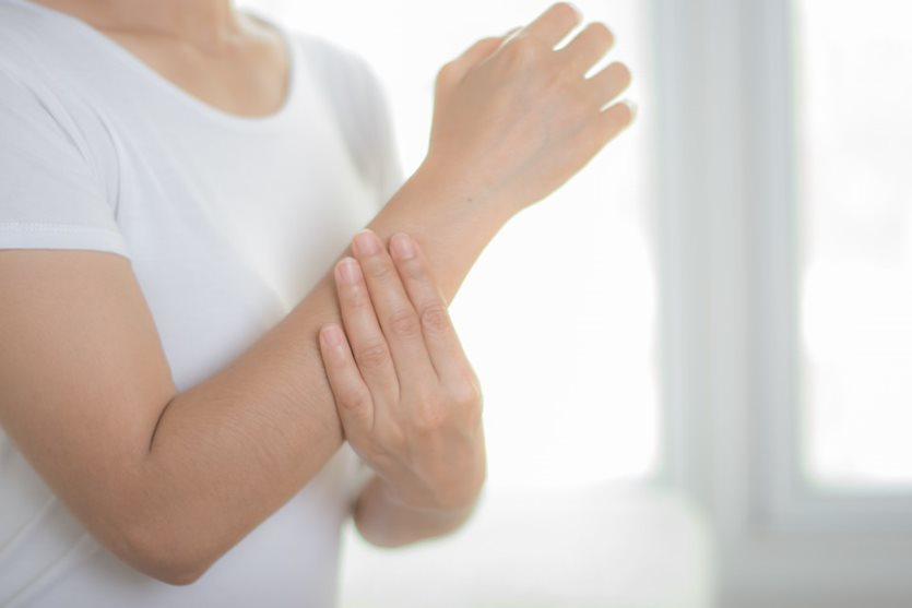 Eine Frau hält sich den Unterarm und verdeckt mit ihrer Hand einen blauen Fleck, der plötzlich aufgetreten ist.