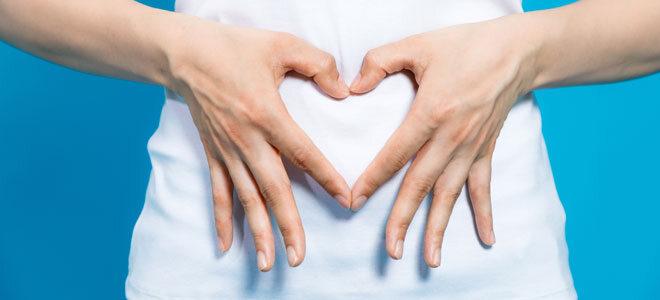 Eine Frau formt mit ihren Händen ein Herz über ihrem Bauch.