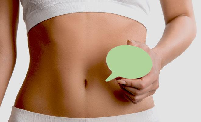 Eine Frau hält eine Fragezeichenblase über ihren Bauch. Sie möchte ihre Darmflora testen lassen.
