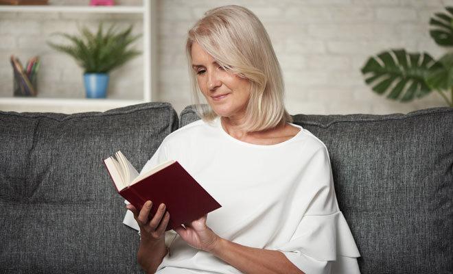 Eine Frau um die 50 liest einen Wechseljahresratgeber.