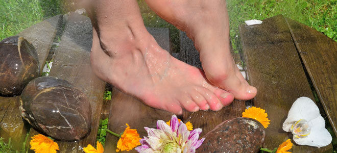 Eine Frau macht einen Kneippguss an den Füßen, um Wechseljahresbeschwerden zu lindern.