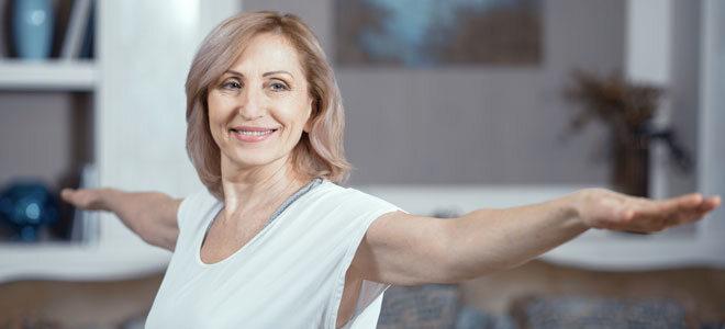 Eine Frau Mitte 50 macht Hormonyoga, um Wechseljahresbeschwerden zu lindern.
