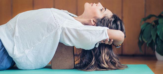 Eine Frau dehnt ihre Schulterblätter mit einem Yogablock