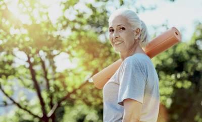 Eine Frau um die 60 trägt eine Yogamatte