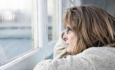 Eine Frau um die 50 sieht nachdenklich aus dem Fenster. Sie leidet an Depressionen in den Wechseljahren.