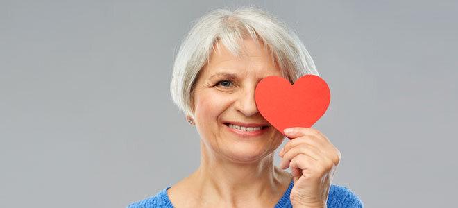 Eine Frau hält ein Herz vor ihr rechtes Auge.