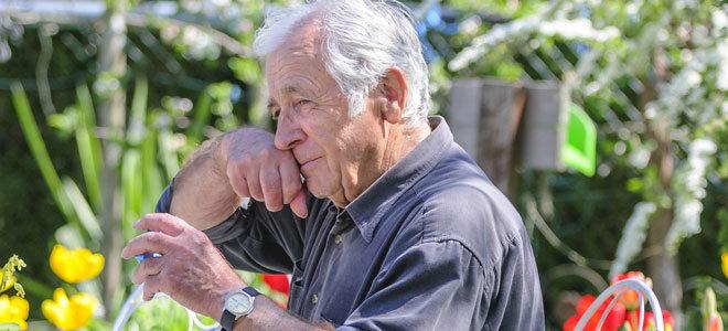 Ein Senior schnupft Tabak im Garten