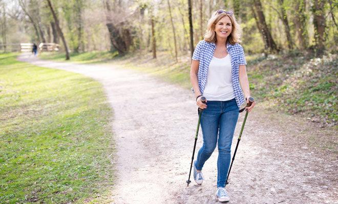 Eine Frau in den Wechseljahren betreibt Nordic Walking