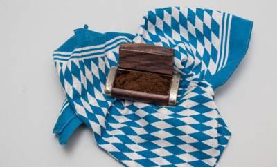 Schnupftabak in einer Dekoschatulle, die auf einem bayerischen Halstuch liegt