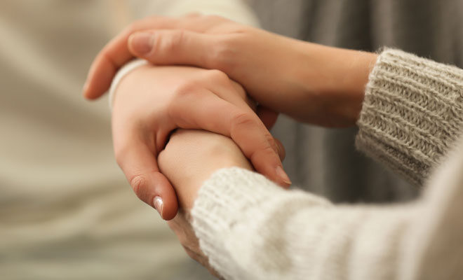 Trauernden helfen: Eine Frau legt ihre Hand auf die Hand einer trauernden Freundin