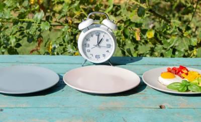 Zwei leere und ein voller Teller, daneben ein Wecker: Sinnbild für die 6:1 Diät.
