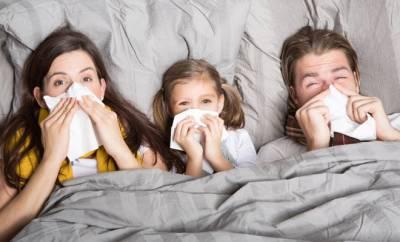 Eine Familie liegt erkältet im Bett.
