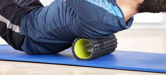 Ein Mann massiert seine Rückenmuskulatur mit einer Faszienrolle mit Noppen