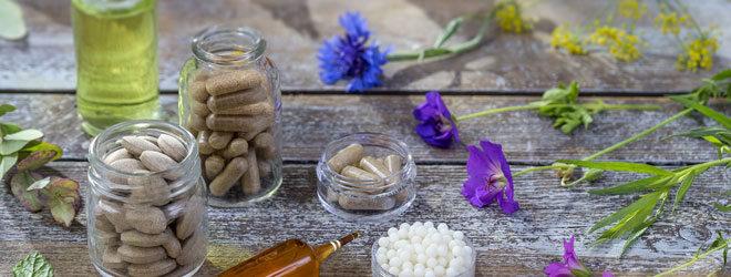 Mehrere Blüten und pflanzliche Arzneimittel auf einem Holzuntergrund