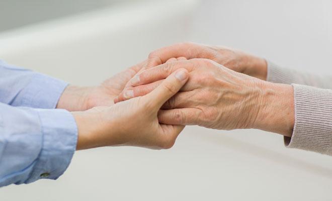 Eine junge Frau hält die Hände einer pflegebedürftigen Seniorin.