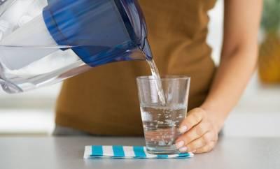 Eine Frau gießt aus einem Wasserfilter Wasser in ein Glas ein.