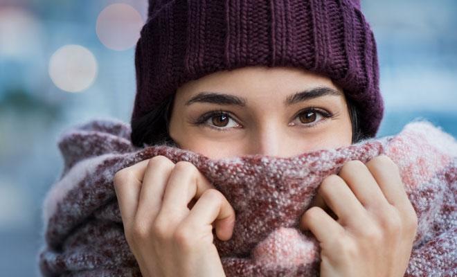 Eine erkältete Frau hüllt sich in ihren Schal