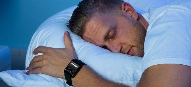 Ein Mann trägt eine Fitness Smartwatch beim Schlafen.