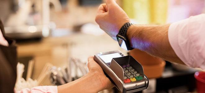 Ein Mann bezahlt elektronisch mit eines Fitness Smartwatch