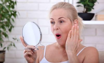 Eine Frau in den Wechseljahren betrachtet ihre Haut im Spiegel