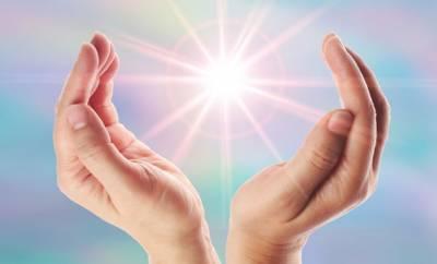 Eine Lichtkugel zwischen zwei Händen