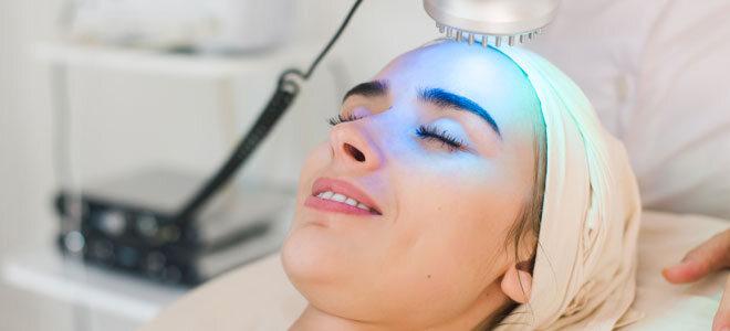 Eine Frau lässt ihr Gesicht mit blauem Licht behandeln.