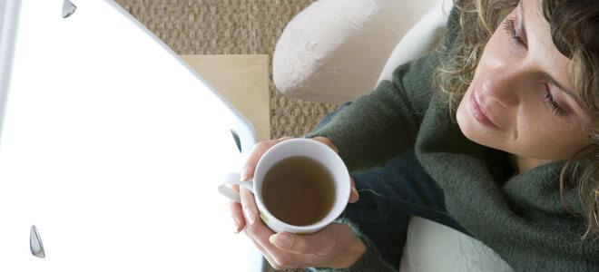 Lichttherapie: Eine Frau sitzt vor einer Tageslichtlampe, um einer Winterdepression vorzubeugen