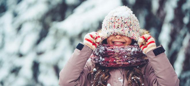 Ein Mädchen trägt Mütze, Schal und Handschuhe im Winter