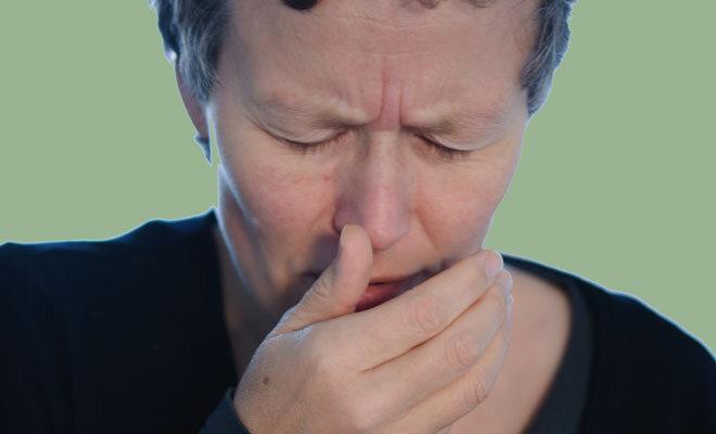 Ein Mann niest in seine Hand. So werden Erkältungsviren schnell weiterverbreitet
