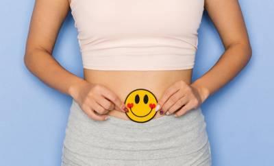 Eine Frau hält ein fröhliches Smiley vor ihren Bauch. Sinnbild für eine gesunde Verdauung