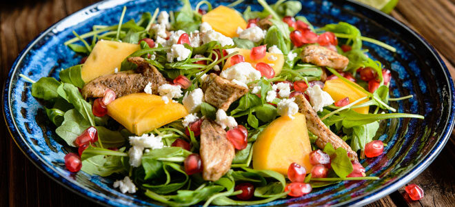 Salat mit Rucola, Feta und Kakis.