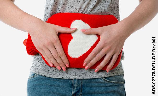Eine Frau hält sich eine Wärmflasche an den Bauch, sie leider unter starken Regelblutungen und damit verbundenen Schmerzen.
