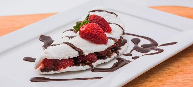 Pfannkuchen aus Tapiokamehl, garniert mit Schokosauce und Erdbeeren.