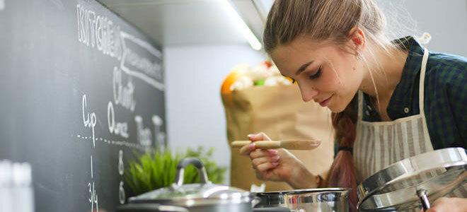 Eine junge Frau kocht einen Eintopf, den sie mit Wacholderbeeren gewürzt hat.