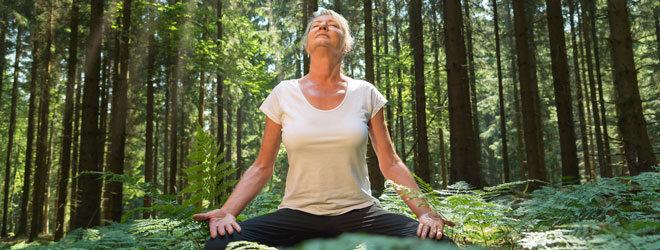 Eine Frau genießt die Ruhe im Wald.
