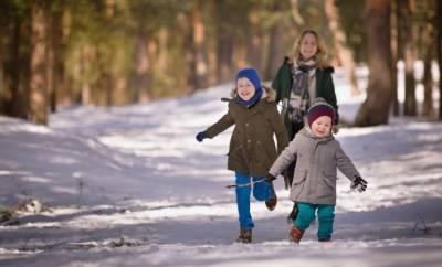 Zwei fröhliche Kinder gehen mit ihrer Mutter im Winter spazieren