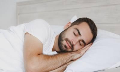 Ein junger Mann schläft gut im Bett. Er achtet auf die richtige Bettenhygiene.