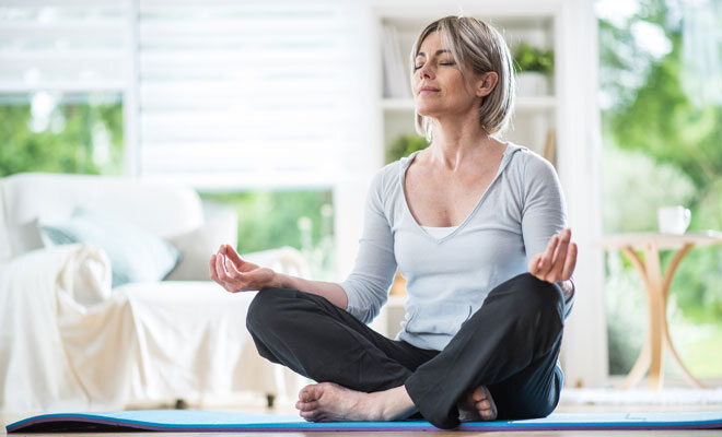 Eine Frau in den Wechseljahren macht Hormon-Yoga, um Wechseljahresbeschwerden vorzubeugen