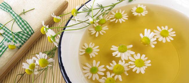 Ein Schüssel warmes Wasser mit Kamillenblüten